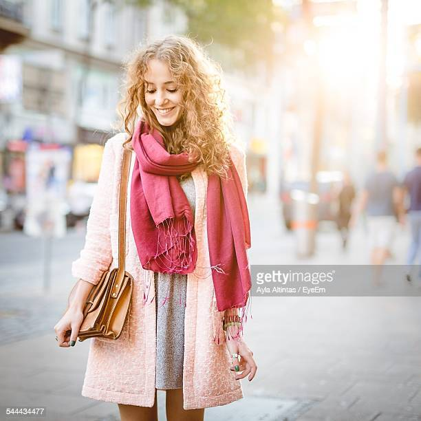 Smiling Woman With Scarf And Purse On Street Looking Down