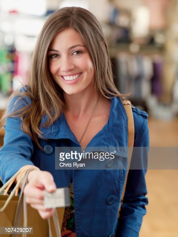 Smiling woman with shopping bag handing credit card : Stock Photo