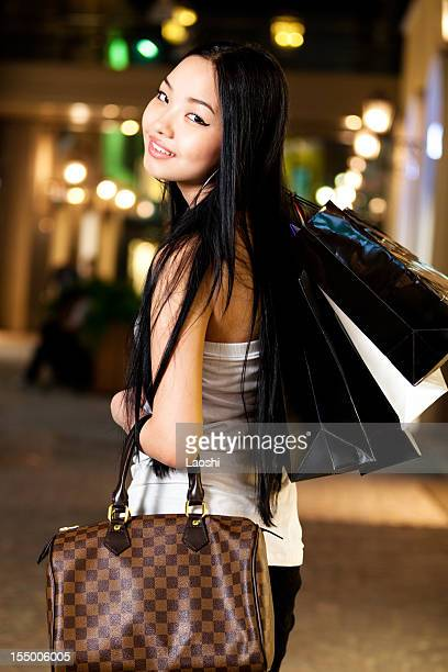 Smiling woman with shopping bags and designer purse