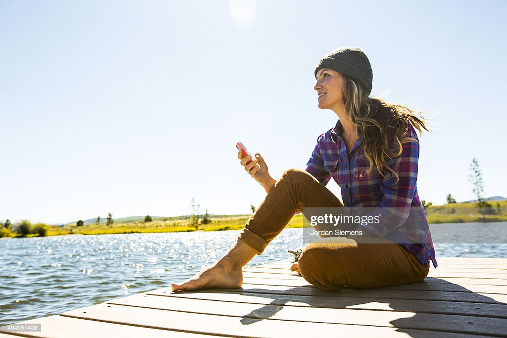 Smiling woman with smart phone on dock : Stock Photo