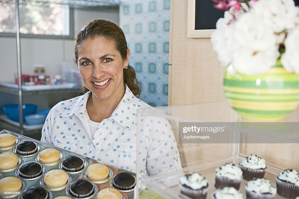 Smiling Woman With Tray Of Cupcakes : Stock Photo