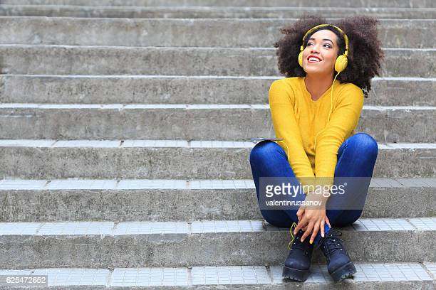 Smiling woman with yellow headphones sitting on stairs
