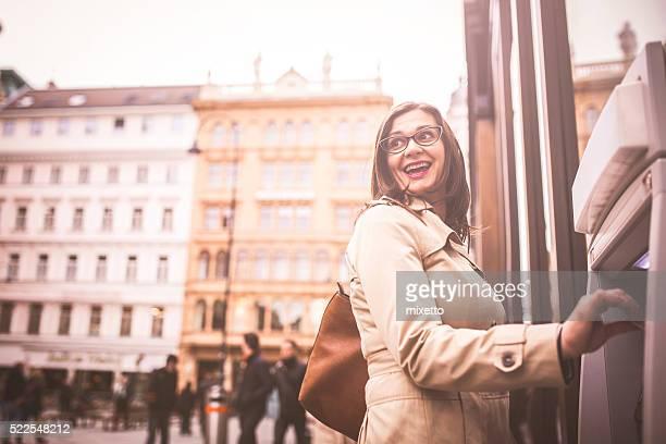 Lächelnde Frau Aberkennung Geld am Geldautomaten