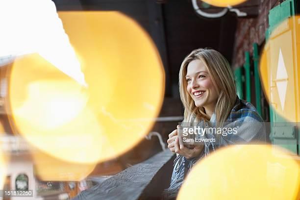 Lächelnde Frau in eine Decke gewickelt und Trinken Kaffee