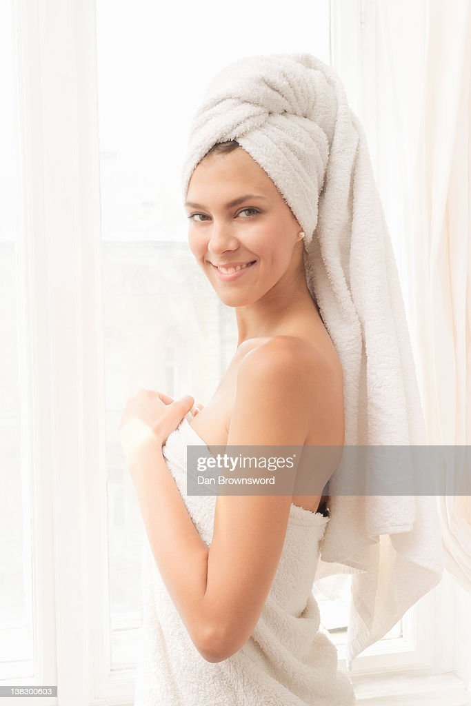 Smiling woman wrapped in towels : Stock Photo