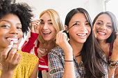 Smiling women applying make up