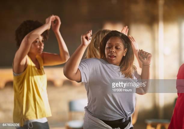 Smiling women dancing in gym.