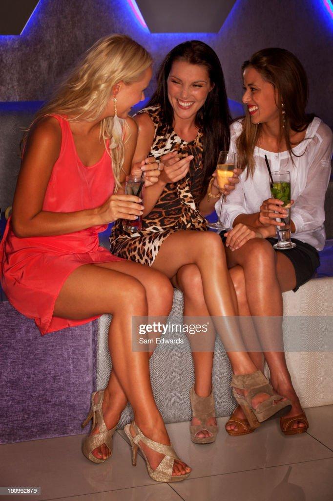 Smiling women drinking cocktails in nightclub