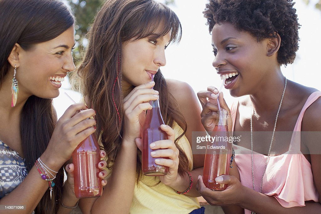 Smiling women drinking soda together : Stock Photo