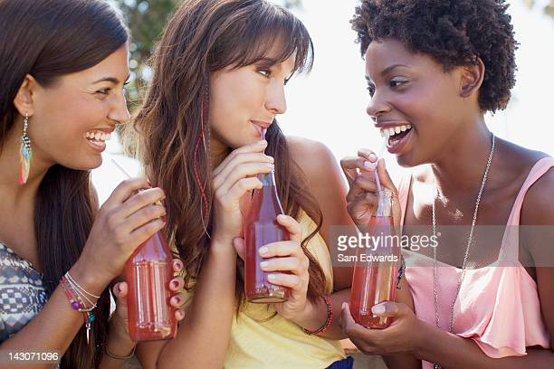 Smiling women drinking soda together
