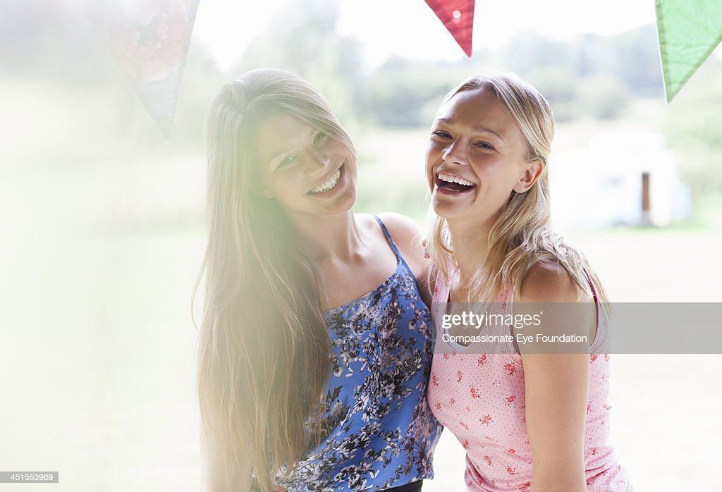 Smiling women embracing outdoors : Stock Photo