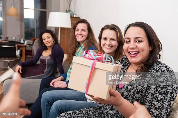 Smiling women handing birthday gift to the viewer