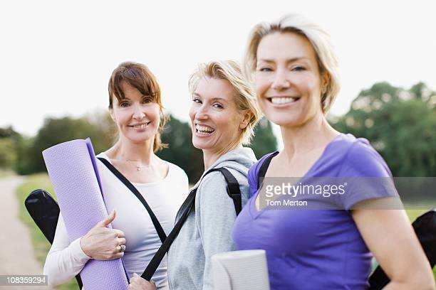 Smiling women holding yoga mats