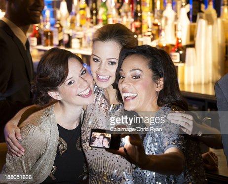 Smiling women hugging and taking self-portrait in nightclub : Stock Photo