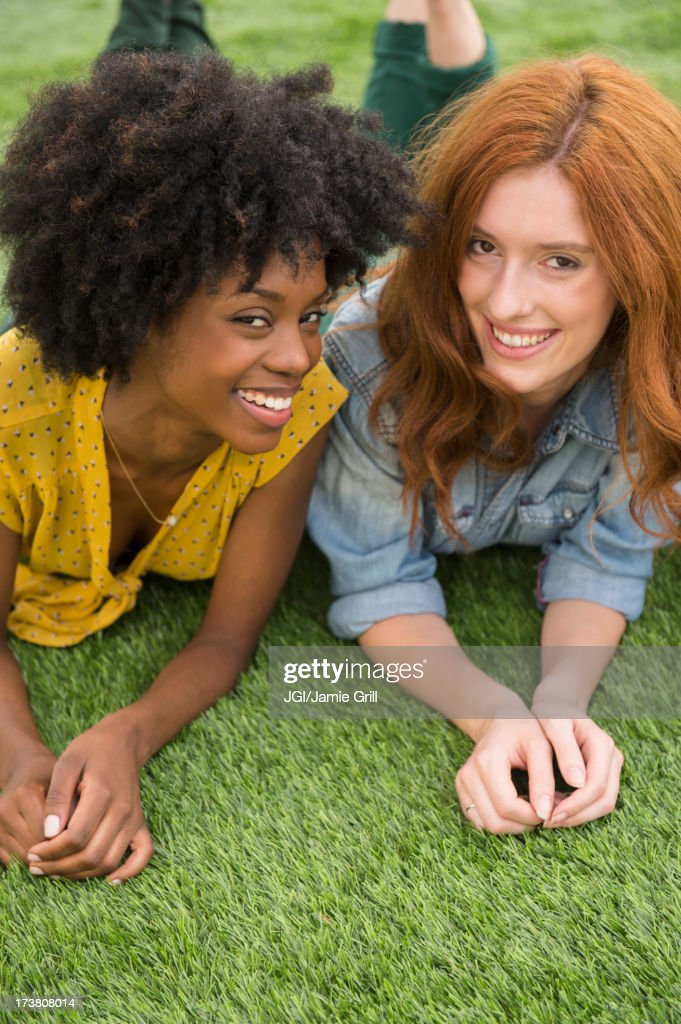Smiling women laying in grass together : Stock Photo
