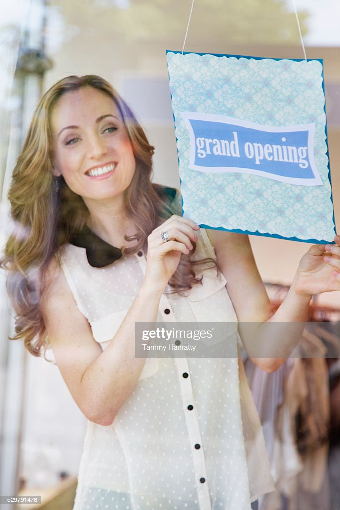 Smiling women putting up open sign : Foto stock