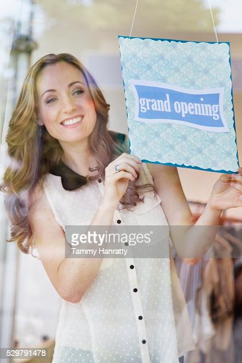 Smiling women putting up open sign : Stock-Foto