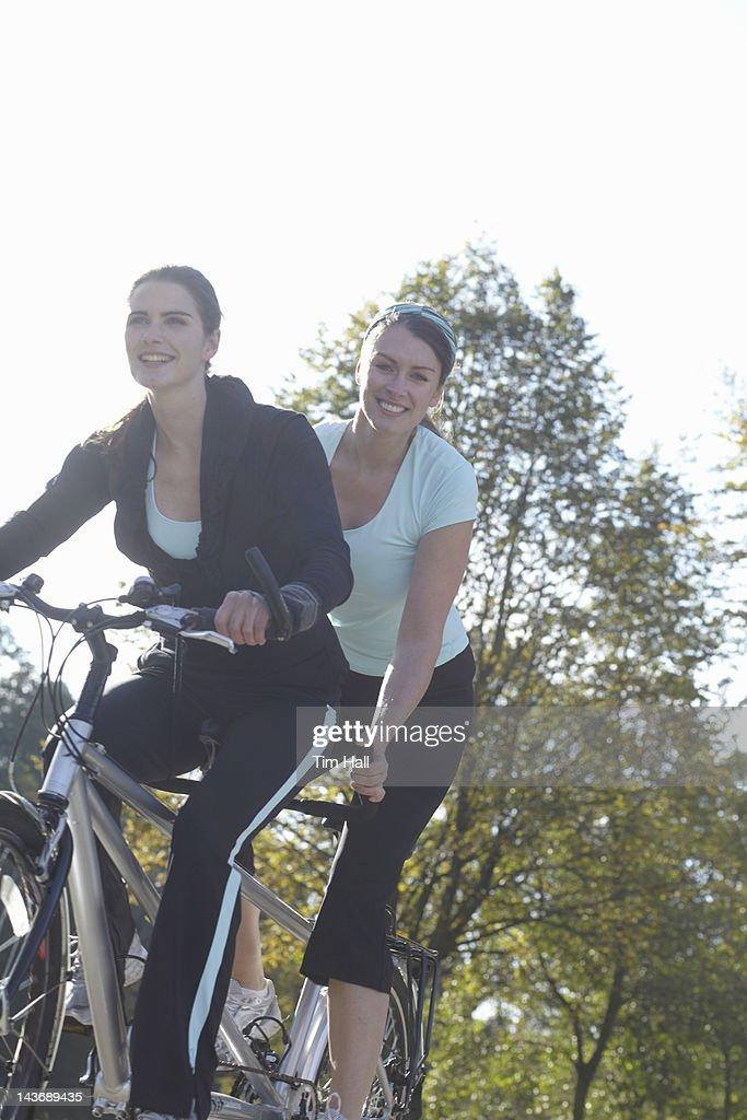 Smiling women riding tandem bicycle : Stock Photo
