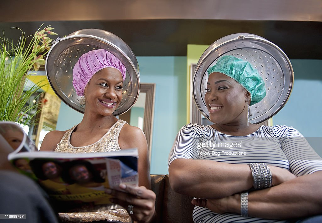 Smiling women sitting under hair dryers in salon : Stock Photo