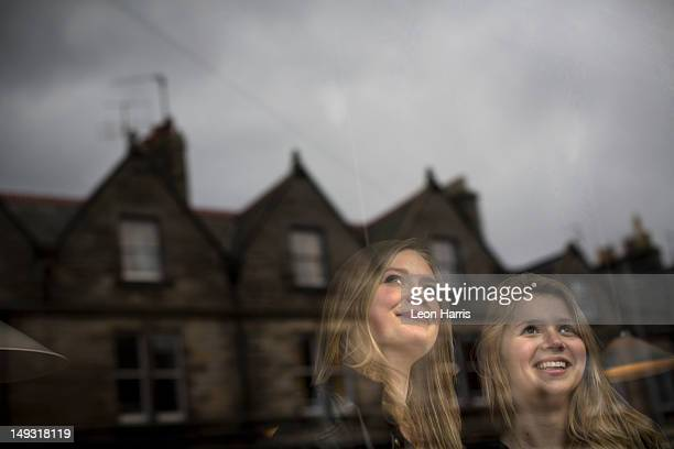 Smiling women standing at window