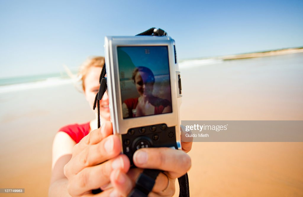 Smiling women takes pictures of herself on beach. : Stock Photo