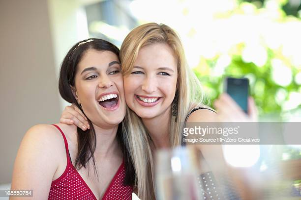 Smiling women taking pictures together