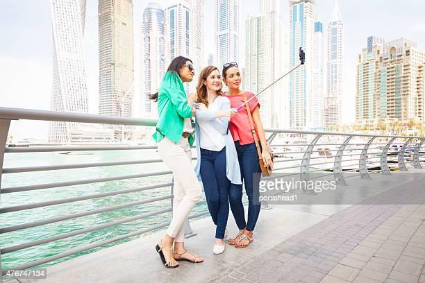 Smiling women taking selfie against cityscape