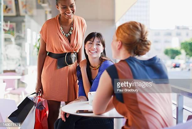 Smiling women talking in cafe