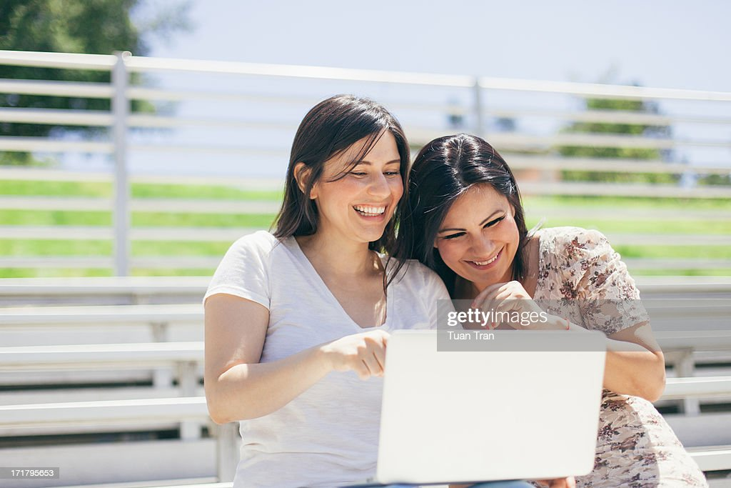 smiling women using laptop together : Stock Photo