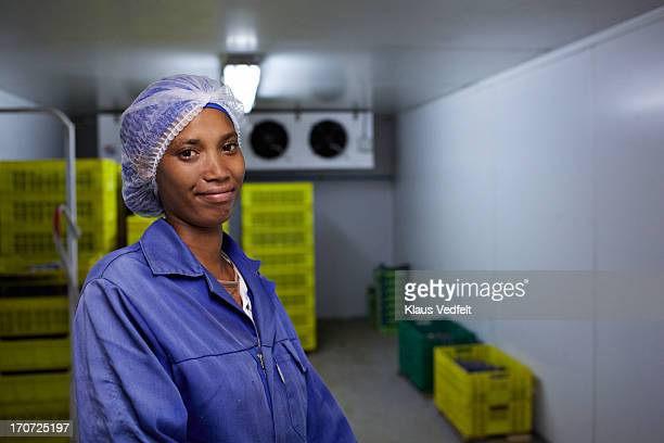 Smiling worker at cold room at small fruit factory