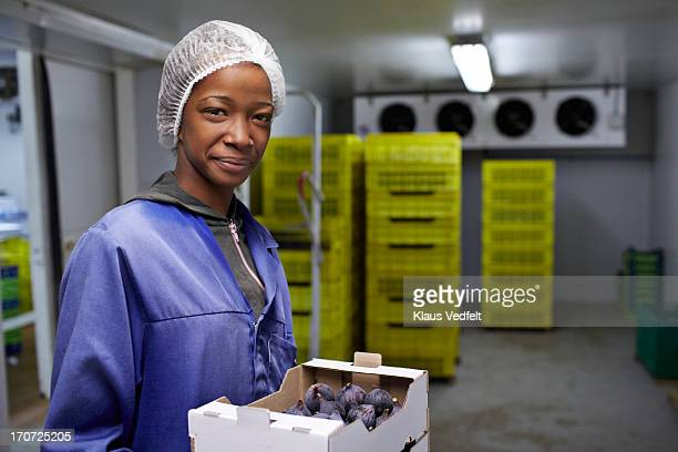 Smiling worker holding boxes of figs in cold room