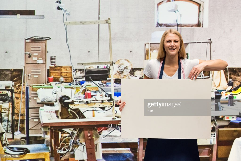 Smiling worker holding placard in textile industry : Stock Photo