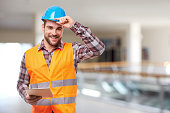 Manual worker in blue helmet with digital tablet