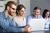 Happy diverse employees watching funny video at laptop during work break in office, male worker showing startup plan or presenting bright idea to excited coworkers during team meeting or briefing