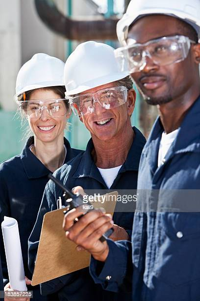 Smiling workers with white hard hats