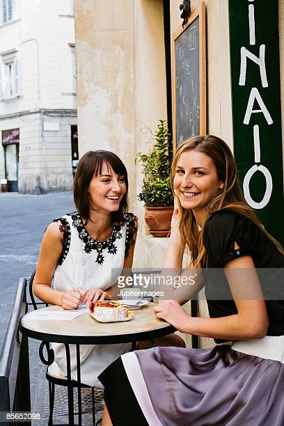 Smiling young adult women at outdoor cafe , Siena , Italy