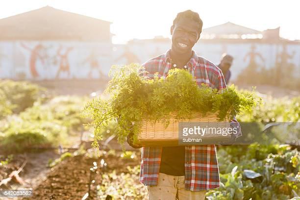 Smiling Young African man holding vegetables Basket