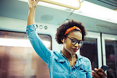 Smiling young African woman listening to music on her cellphone while standing on a subway train during her daily commute