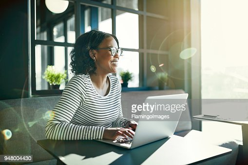 Smiling young African woman working online with her laptop : Stock Photo