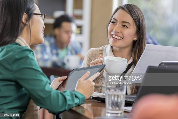 Smiling young Asian businesswoman meets with colleage