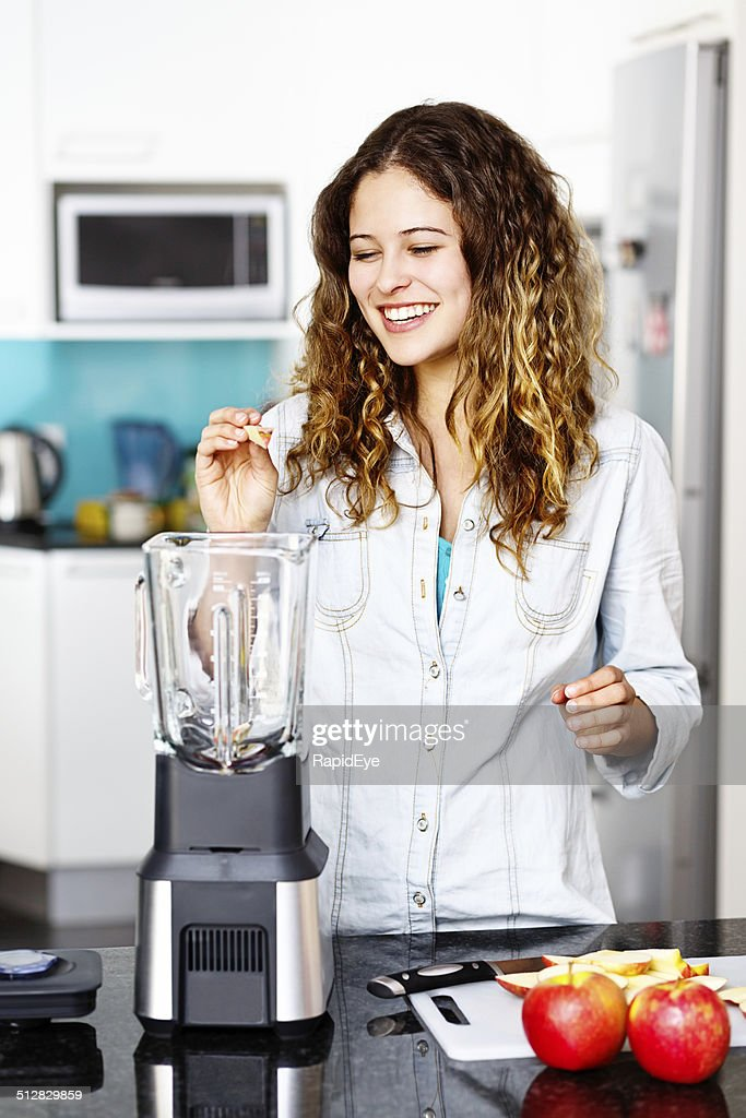 Smiling young beauty busy with kitchen blender