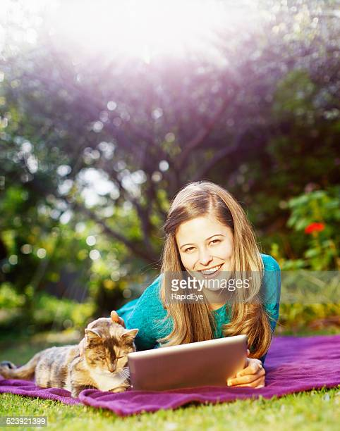 Smiling young beauty with cat and digital tablet in garden