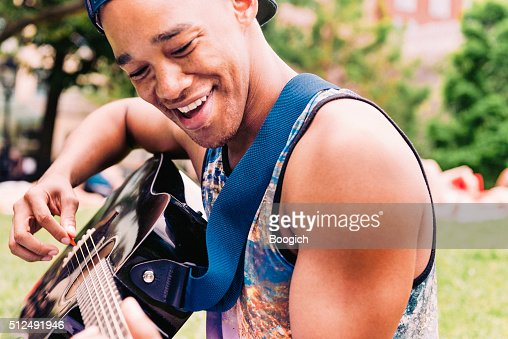 Smiling Young Black Man Playing Acoustic Guitar in NYC Park