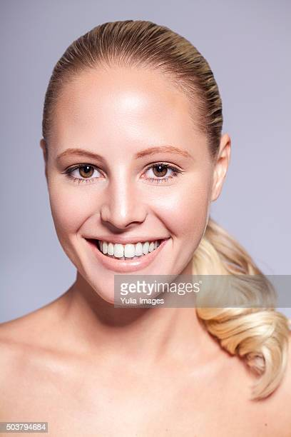 Smiling Young Blond Woman with Hair in Pony Tail