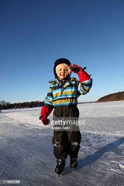 Smiling young blonde girl skating on lake