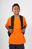 School boy, 11, with big happy smile ready for school wearing bright orange t-shirt and back pack. Studio shot against white background - Canon 5D MKII