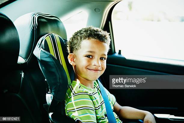 Smiling young boy buckled in car seat in car