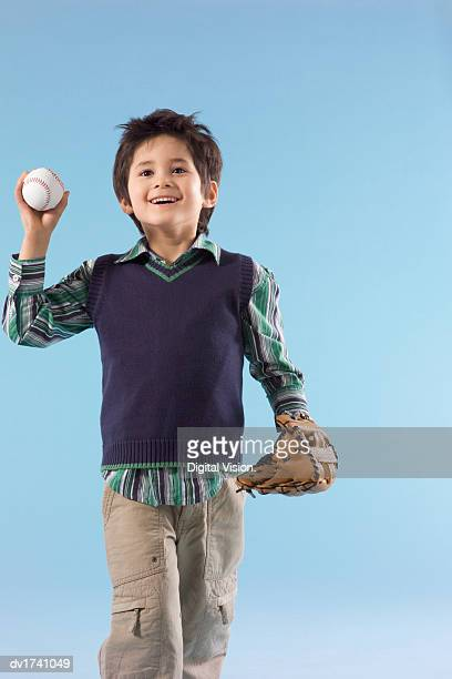 Smiling Young Boy Holding a Baseball and Baseball Glove
