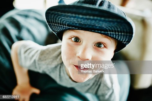 Smiling young boy leaning off chair in living room : Stock Photo