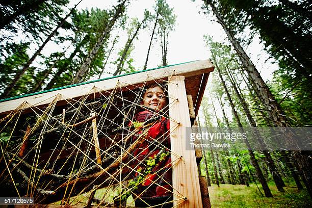 Smiling young boy sitting in fort at summer camp